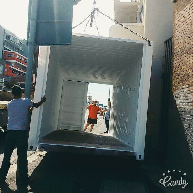 Two Guys Hold A Shipping Container As Its Placed On The Ground