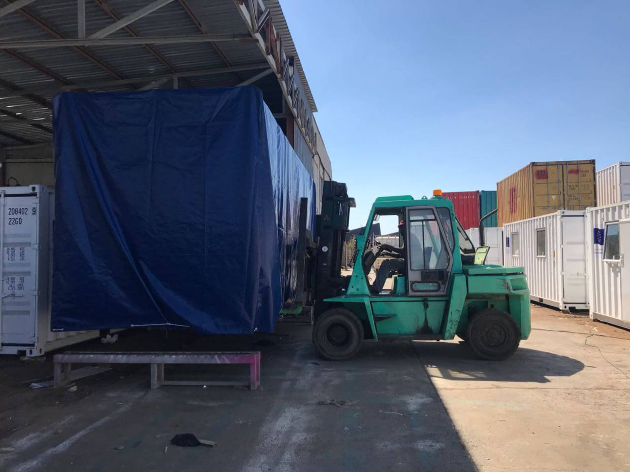 Forklift Lifting A Shipping Container | Container Rental & Sales