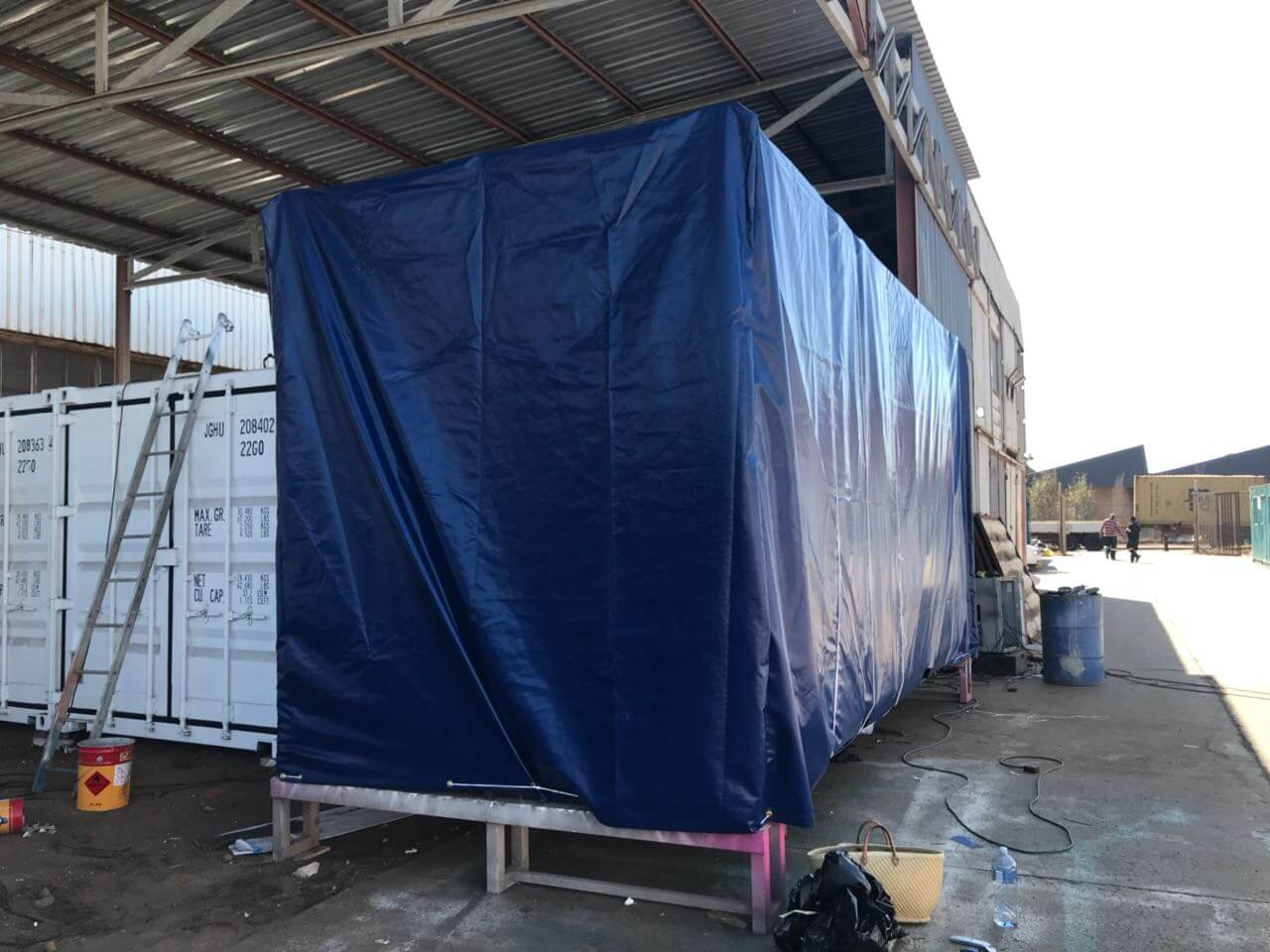 Container Wrapped In A Blue Tent | Container Rental & Sales